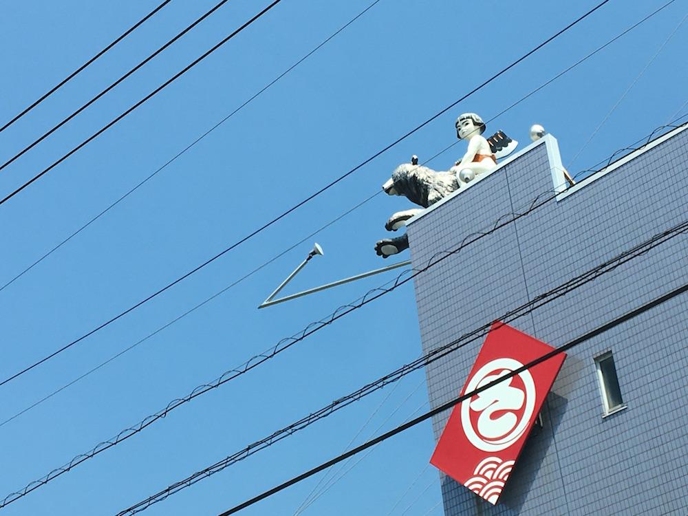 ビルの上で店の看板の役割をする「金太郎」。熊にまたがる姿が愛らしい