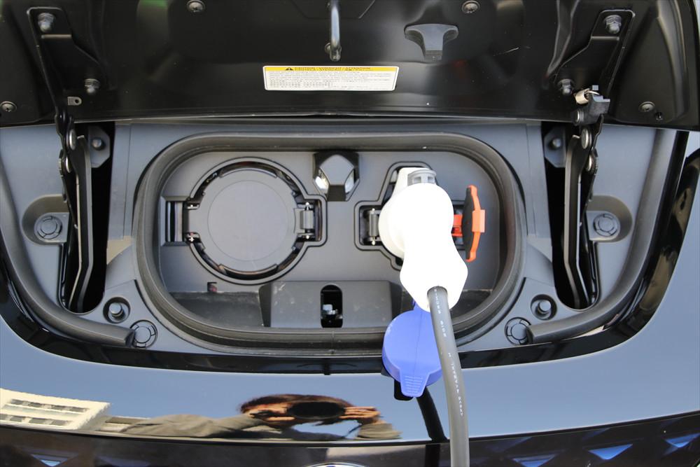 クルマの前部にある充電口に接続されているプラグを抜き、充電口のカバーを閉じる