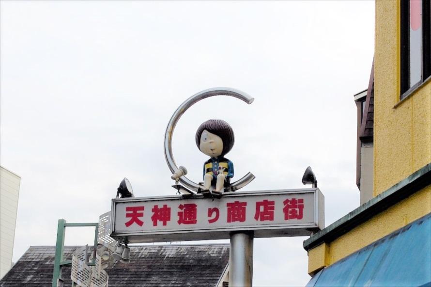天神通りの両端にある街灯の上で、鬼太郎は通行人をながめている