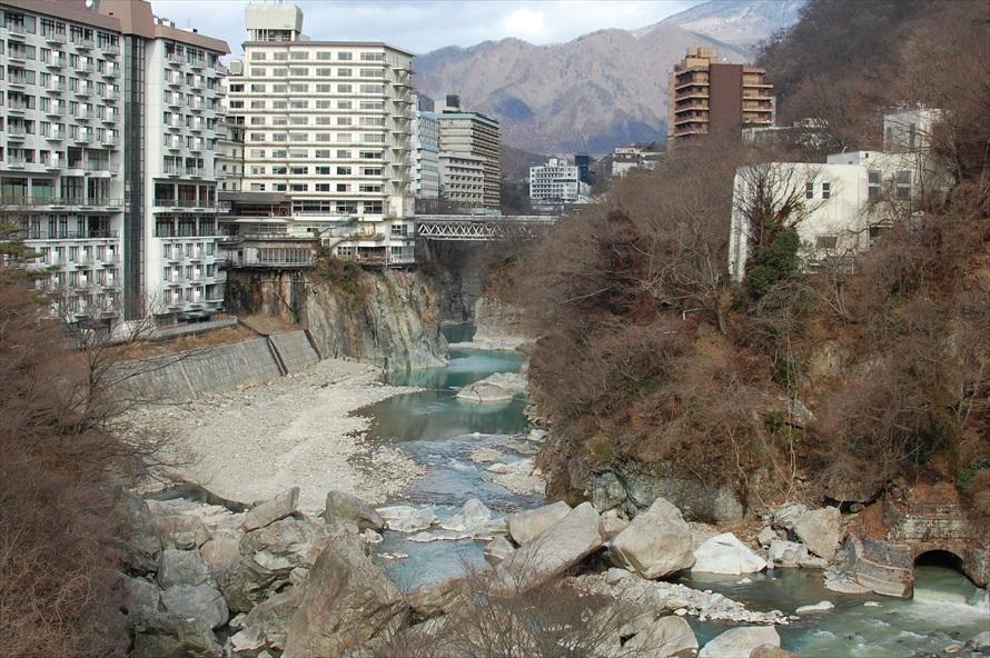 温泉街らしい景色が広がる。川沿いには日帰り温泉が楽しめるホテルも