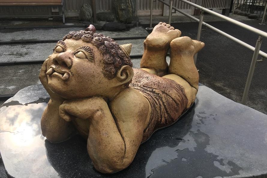 くろがね橋近くにある足湯「鬼怒子の湯」の前で寝そべる遊心鬼。片方のツノにリボンを結んだ、おしゃれな女の子の鬼