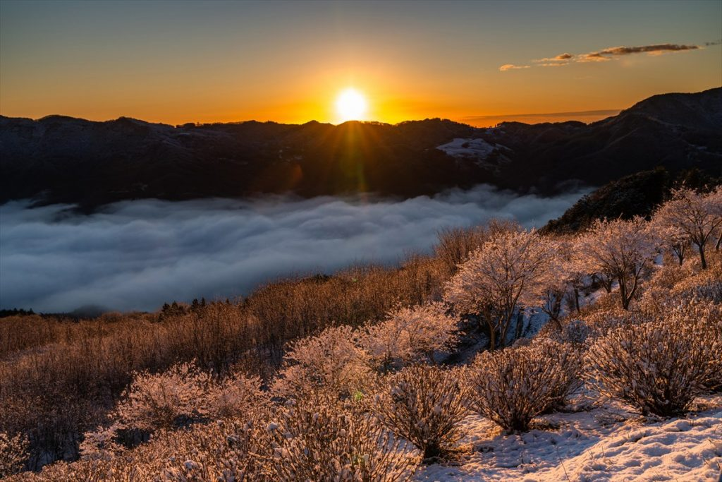 山々から顔を出す朱色の太陽。眼下には秩父エリアが一望できる