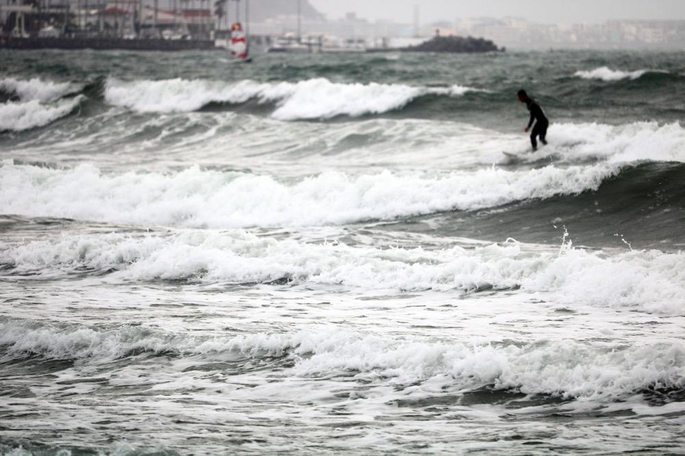 荒れ気味の海でも楽しそうに浜から海へと入っていくサーファーたち